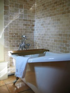 Slipper bath set in travertine tiled bathroom