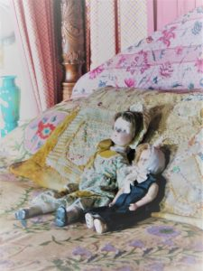 four poster bed dressed fro film with old dolls