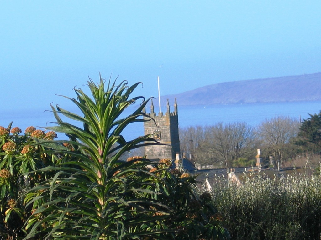 Perranuthnoe church framed by blue seas seen from Ednovean Farm