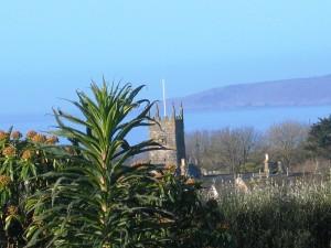 Perranuthnoe church framed by blue seas seen from Ednovean Farm
