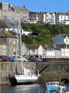 An elegant yatched moored under the tall sea wall of Porthleven Harbour