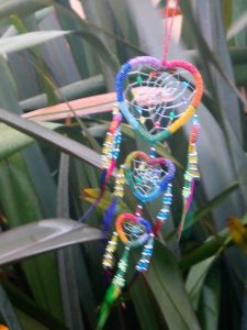 A brightly coloured dream catcher blowing in the wind and rain part of the garden dressing for ednovean farm's garden ready for filming