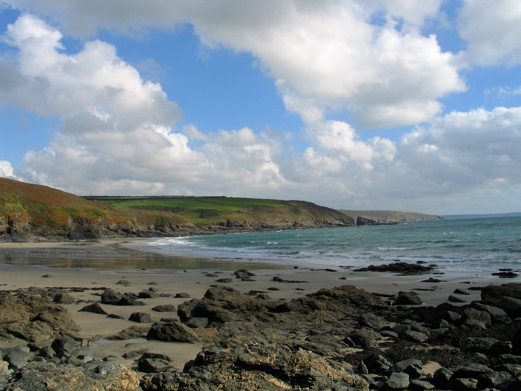 rocks leading to a beach of golden sands framed by farmland in Cornwall