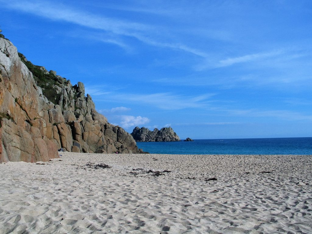 The fine sands made of crushed shells stretch to blue sky and sea at Porthcurno