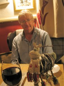 man at a pub table with glass of wine and christmas decotations