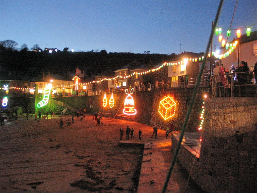 Children playing in the harbou among the christmas light of Mousehole