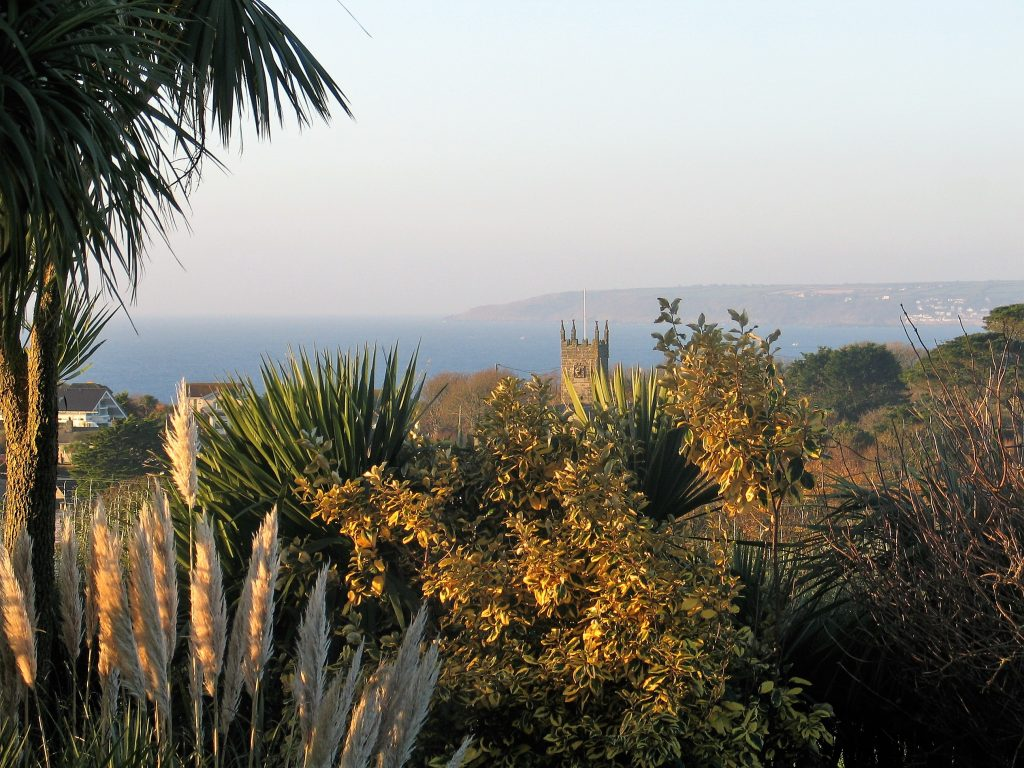 The blue seas and golden foliage of autumn beyond the garden at Ednovean Farm
