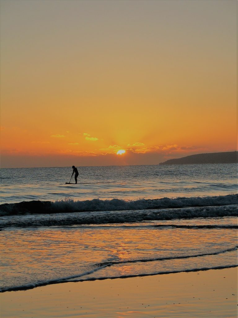 waves curling on to the shroe witha paddleboarder in the sunset over the sea