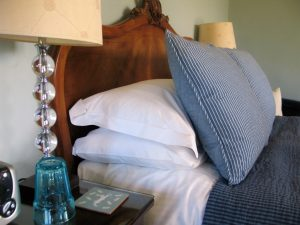 Plump cushions and fresh whtie pillows dress a bed for hygge
