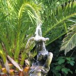 August the summer fountain and lush Date palms