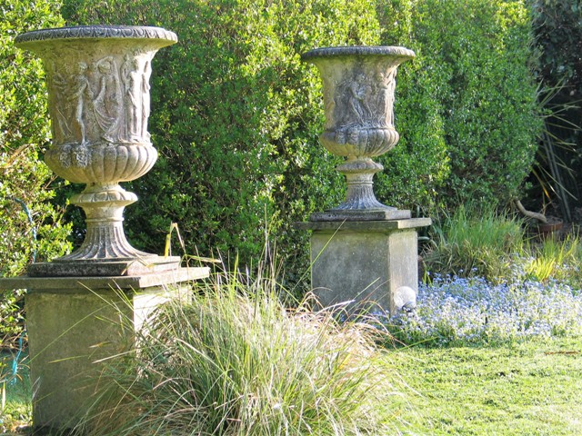 Spring light in the gardne on urns set in forget-me nots