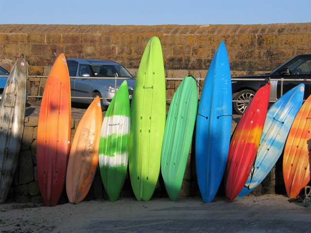 brightly coloured surfboards stacked beside a cornish harbour