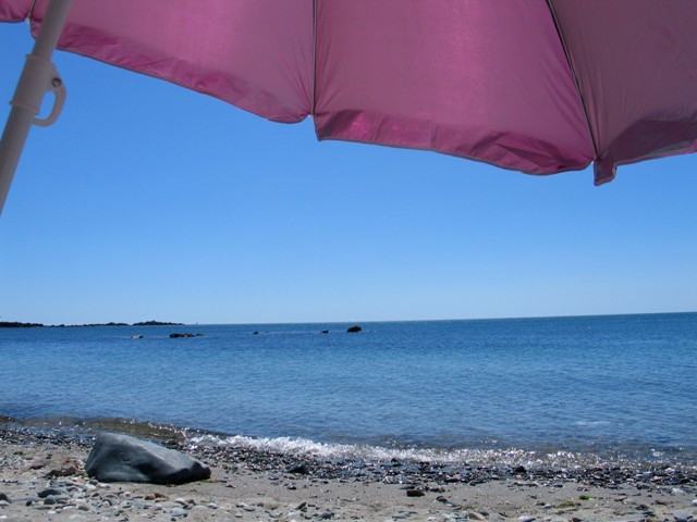 Bright pink sun parasol beside blue seas