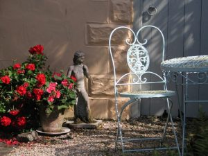 Garden cahir, Geraniums and statue - august sunshine in a courtyard