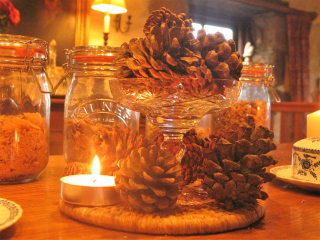 Breakfast table centrepiece of fir cones and candles