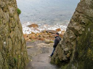 Glimpse of sea churning over rocks at the base of steps