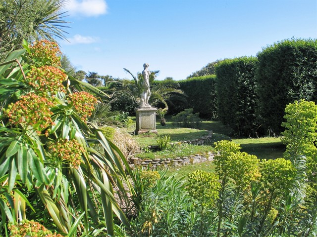 Statue in formal garden with spring flowers