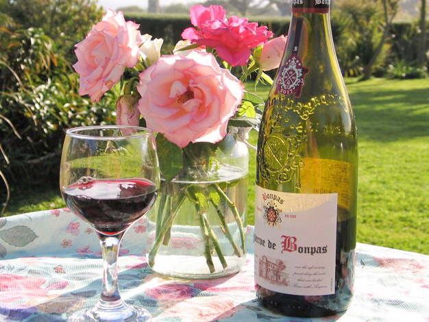 Roses and wine glass on garden supper table